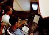 Астронаутите Дејвид Скот и Џејмс Ирвин вежбаат навигациски маневри во симулаторот за возење на месечевиот ровер, заедно со  астронаутот Џозеф П. Ален, некој ден пред да тргнат кон Месечината